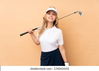 Teenager Russian girl isolated on beige background playing golf