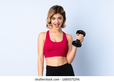 Teenager Russian girl making weightlifting isolated on blue background with surprise and shocked facial expression