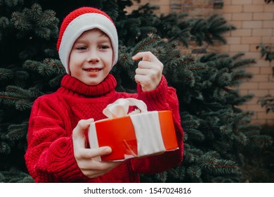 A teenager in a Santa Claus costume holds a gift and shows a sign Fig. Christmas tree for the New year. Happy child. A Bad Christmas.