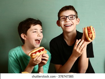 teenager school boys cooking eat hot dog happy smiling laughing closeup portrait on blue wall background