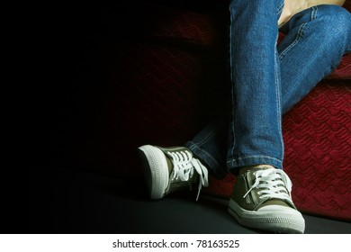 A Teenager showing her shoes and jeans, posing in studio.
