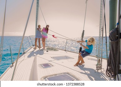 Teenager sisters playing tag of war with young brother child on luxury yacht on sailing trip holiday, sunny outdoors. Family tourists games, aspirational leisure recreation travel lifestyle.