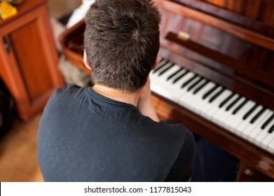 The teenager sits behind the piano with his back to the camera. He was exhausted, he was already tired of playing the piano because he was lazy. The boy yawns and wants to sleep