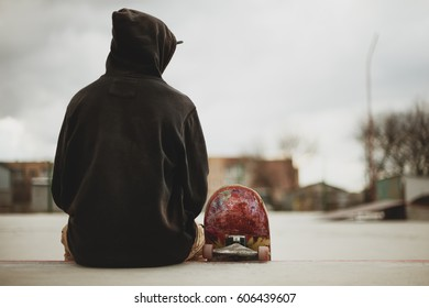 Teenager sitting in a black sweatshirt holding a skateboard on a slum background urban