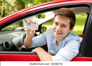 teenager sitting in new car and shows his drivers license
