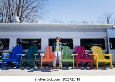 Teenager sitting on colourful Adirondack chairs