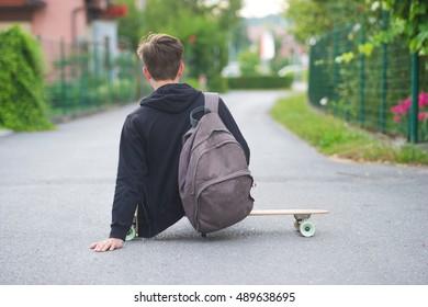 Teenager sitting on his longboard on the street.