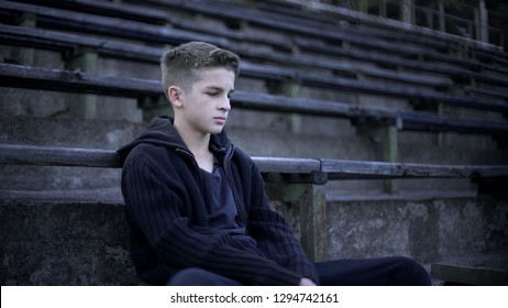 Teenager sitting on stadium tribune, devastation and poverty, city after war