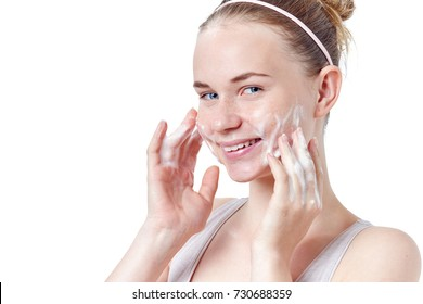 Teenager skincare. Smiling beautiful redhead teen girl with freckles and blue eyes using foaming cleanser. Face washing concept isolated on white background.