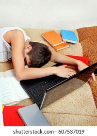 Teenager sleep with the Books and Laptop on the Sofa at the Home