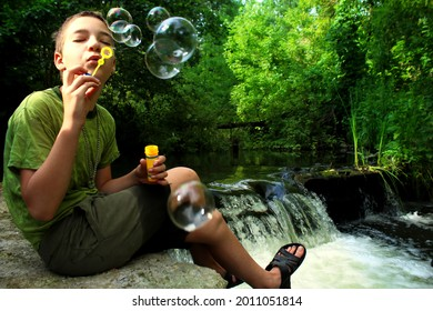 teenager with soap bubbles on a river waterfall.