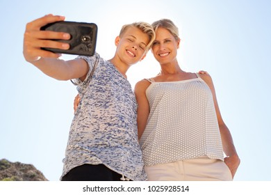 Teenager son and mother posing taking selfie photo with smart phone on destination nature holiday, outdoors. Family day out using technology, travel leisure recreation lifestyle, heads together.