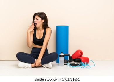 Teenager sport girl sitting on the floor yawning and covering wide open mouth with hand
