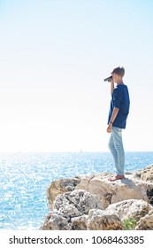 Teenager standing on sea cliff using binoculars contemplating the blue sea and sky on holiday, outdoors. Young man looking through binoculars, adventure discovery travel recreation leisure lifestyle.