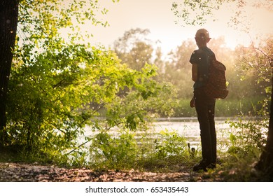 A teenager stands on the river bank
