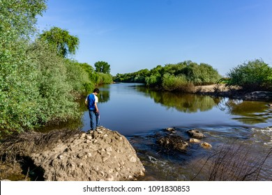 The teenager stands on top of a large stone boulder on the bank of the Sorraia River and looks at the river below. The river Sorraia in the summer - bright green vegetation,  blue sky.