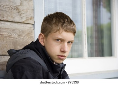 teenager staring into space - in front of a window