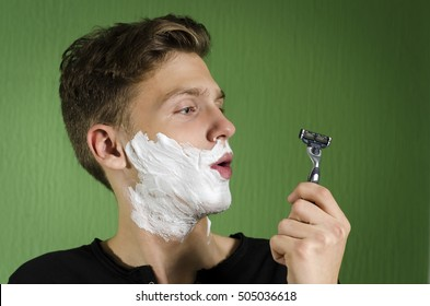 Teenager starting to shave, confused, looking at razor