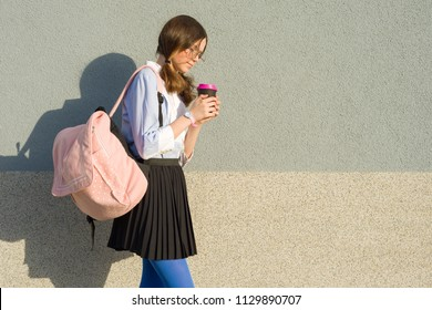 Teenager student girl with school backpack and glass of drink, in profile, background an outdoor gray wall, copy space.