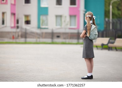 A teenager student girl stays near a school looking at her school buiding. Back view. Schoolgirl wearing medical face mask and carrying a mint backpack. Children coming back to school after pandemic.