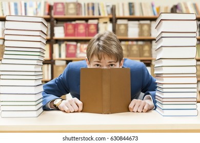 Teenager student preparing for exams at the library. Worried. Looks out from behind the book and looks into the camera