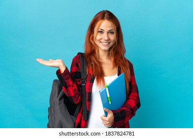 Teenager student Russian girl isolated on blue background holding copyspace imaginary on the palm to insert an ad and with thumbs up