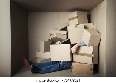 teenager student in small office littered with boxes, concept - too much work, Male feet under a heap of carton boxes