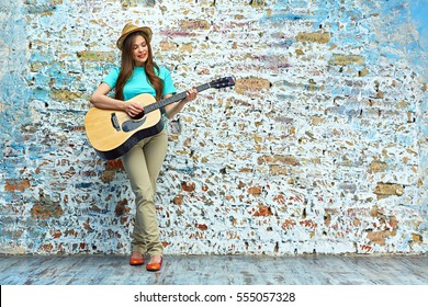 teenager style portrait of young woman playing acoustic guitar against brick wall