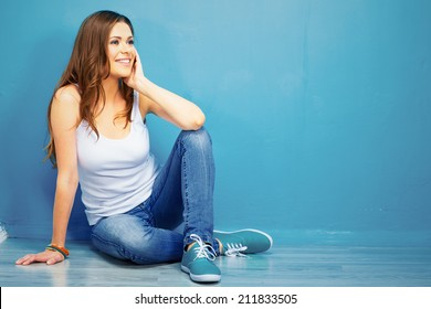 teenager stylish model full body portrait sitting on floor . smiling young woman .