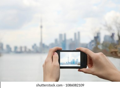 Teenager taking photo Beautiful Skyline view of Toronto downtown with mobile cell phone