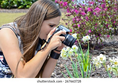 A teenager taking a photograph of her garden flowers.