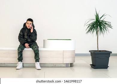 Teenager talking on smartphone in modern commercial center. Bench and flower in a pot. Modern building interior. Technology and communication concept with child in contemporary building interior.