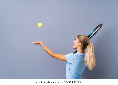 Teenager tennis player girl over grey wall