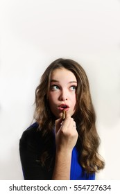 Teenager thinking while putting on lipstick