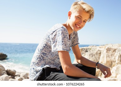 Teenager tourist male relaxing on rocky beach on holiday, looking smiling at camera against sunny blue sky, outdoors. Healthy young man enjoying nature, travel adventure leisure recreation lifestyle.