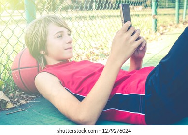 teenager use smartphone with friends for play basketball outdoor - healthy sporty teenagers lifestyle concept