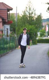Teenager  using his longboard on a suburban street.