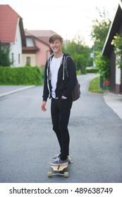 Teenager wearing a bag skateboarding with a longboard.