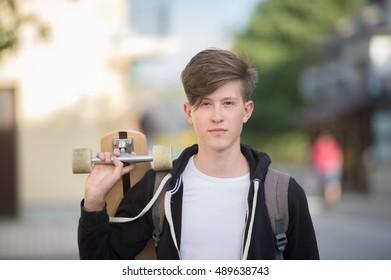 Teenager wearing a black hoodie holding a longboard on the street.
