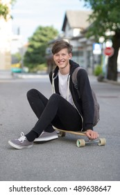 Teenager wearing a black hoodie and white t-shirt sitting on his longboard and smiling.