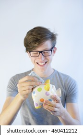 Teenager wearing glasses smiling and putting money into his piggy bank.