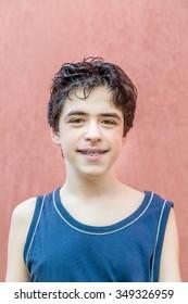 teenager wearing vest smiles showing braces