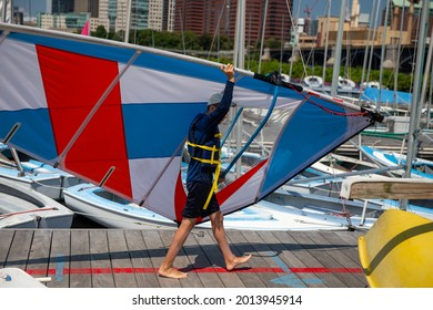 Teenager with windsurfing equipment on a pier.