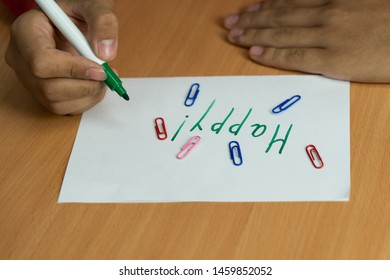 """teenager writes with the marker on the white sheet at the table the word """"happy"""""""