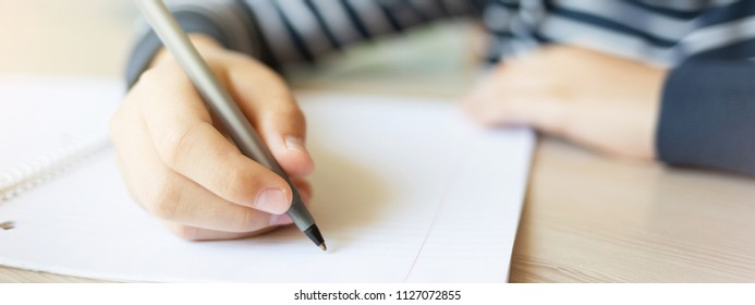 Teenager writing in notebook. Close up, banner for website, back to school concept.
