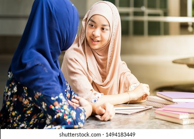 Teenager Young Adult Asian Thai Muslim university college student reading book together using for education concept