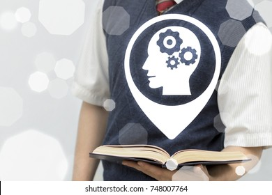 Teenager (young student, scientist, schoolboy) holds book with head gears location icon on a virtual screen. Brainstorm Knowledge System Educational concept.