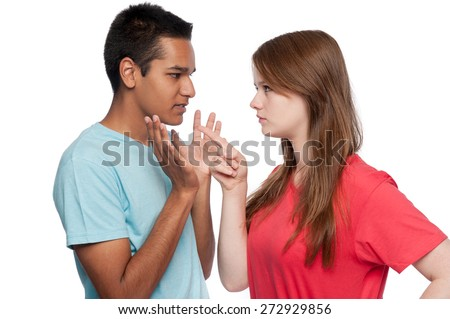 Teenagers in argument. Girl accusing. Boy defending. Studio shot. White background.