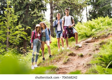 Teenagers with backpacks hiking in forest. Summer vacation.