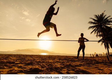 teenagers balance jumping on slackline with risk on sunrise beach silhouette